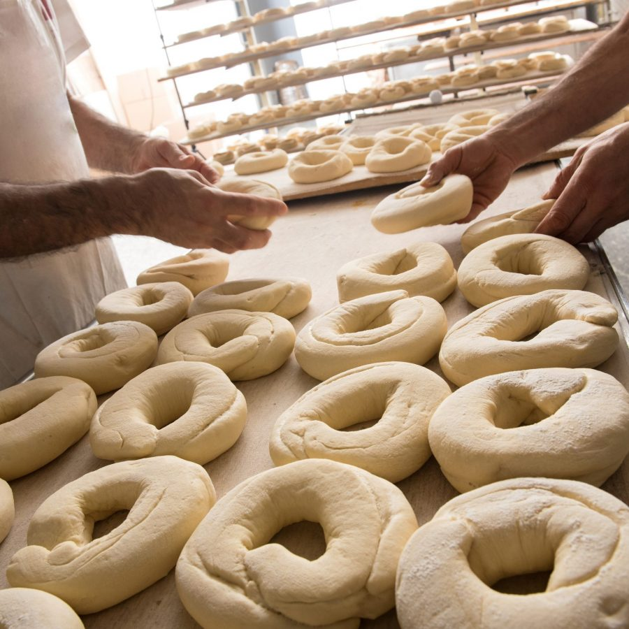 Two male bakers placing dough for bagels on baking table in bakery